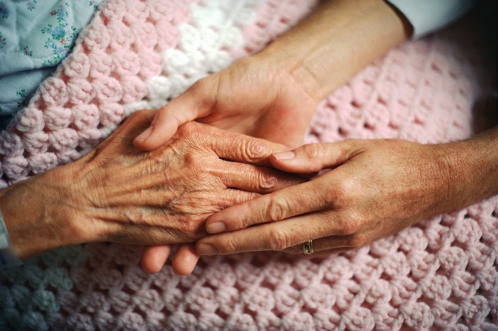 A geriatrician holds the hand of an elderly woman with arthritis.