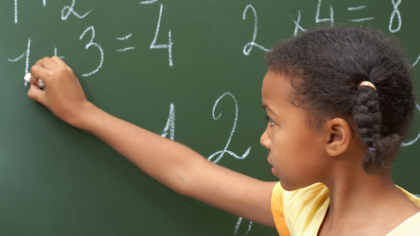 child doing mathematics on a chalk board at school (education)