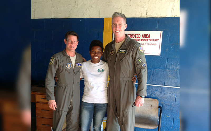 USAID - Noellea Sankar of Good News in St. Lucia (center), poses with U.S. Air Force pilots, Quentin Miller (left), and William Thompson (right).