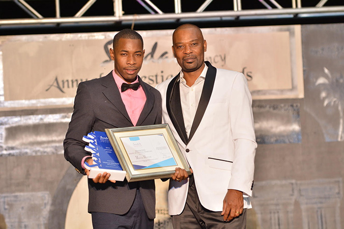 Marcus Monrose receives the Diamond Talent of the Year Award from Hotel Manager at Sandals Regency LaToc Mr. Stephen Husbands