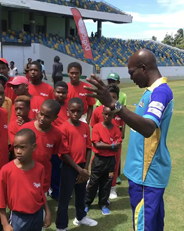 Barbados Tridents Assistant Coach, Vasbert Drakes, explaining the fundamentals about the game of cricket to the kids