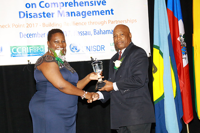 The Hon. Samantha Marshall, Minister of Social Transformation and Human Resource Development, Antigua and Barbuda and Chair of the CDEMA Council of Ministers (left) presenting the CDEMA Council Award to General Earl Arthurs