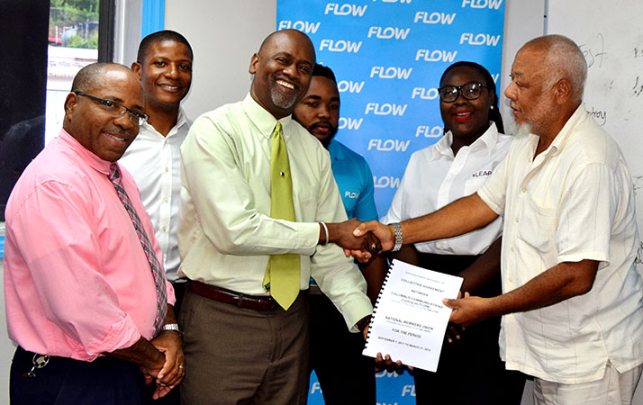 Labour Commissioner, Ray Narcisse (left) with representatives of Flow management and staff, and the National Workers Union